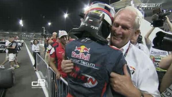 Helmut Marko y Kvyat se abrazan. Están tapando bocas.